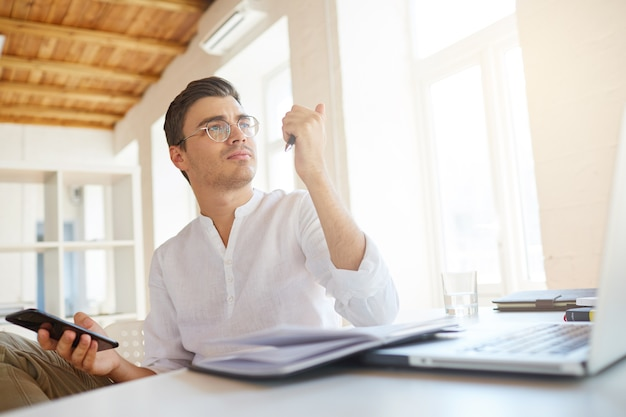 Nahaufnahme des nachdenklichen ernsten jungen geschäftsmannes trägt weißes hemd im büro