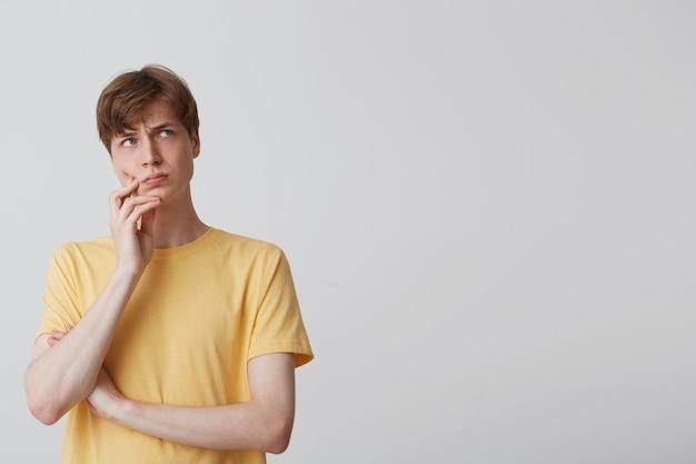 Nahaufnahme des nachdenklichen gutaussehenden jungen mannes trägt gelbes t-shirt stehend, hält hände gefaltet und denkt isoliert über weiße wand