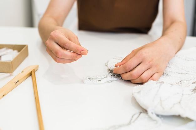 Nahaufnahme des nähenden kleides der modedesigner hand über schreibtisch