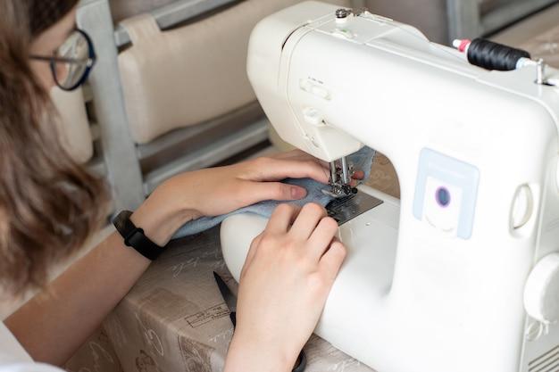 Nahaufnahme des nähens an einer nähmaschine, selektiver fokus. das mädchen mit brille näht kleidung. das konzept eines hobbys, design, eigenkreation exklusiver dinge