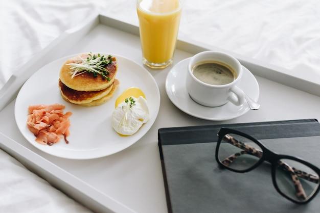 Nahaufnahme des nahrhaften und leckeren frühstücks mit kaffee im bett auf tablett mit gläsern und buch