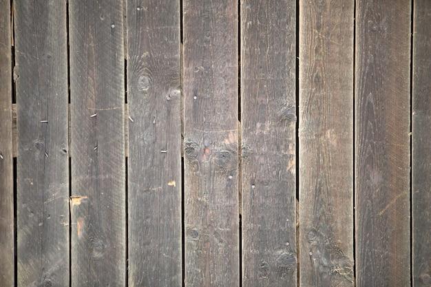 Nahaufnahme des natürlichen alten weinlese verwitterten graubraunen unbemalten massiven holzzauns oder des tores von planken und brettern. vertikaler kopienraum der ökologischen beschaffenheit sonniger geknisterter hintergrund.