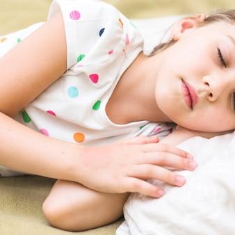 Nahaufnahme des netten kleinen mädchens, das auf bett schläft