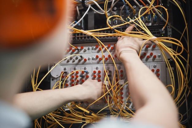 Nahaufnahme des netzwerkingenieurs, der kabel im serverraum während der wartungsarbeiten im rechenzentrum anschließt, platz kopieren
