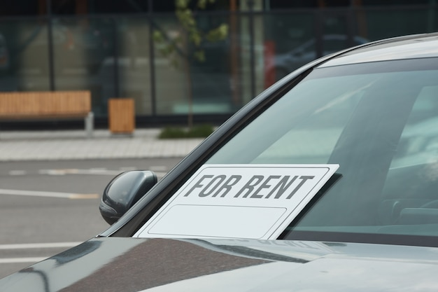 Nahaufnahme des neuen autos mit plakat auf dem fenster, das zur miete vorgeschlagen wird