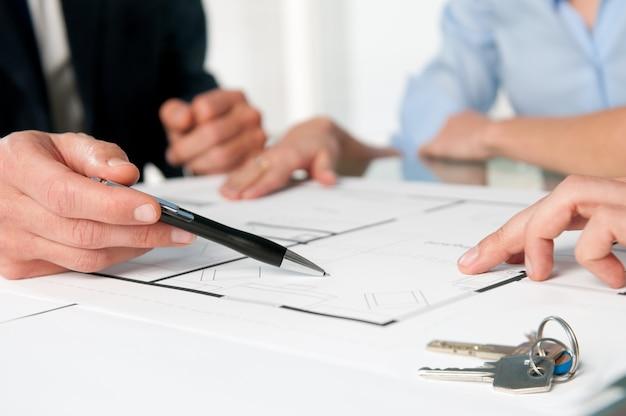 Nahaufnahme des neuen hauptschlüssels und des hausplans während einer diskussion mit einem immobilienmakler
