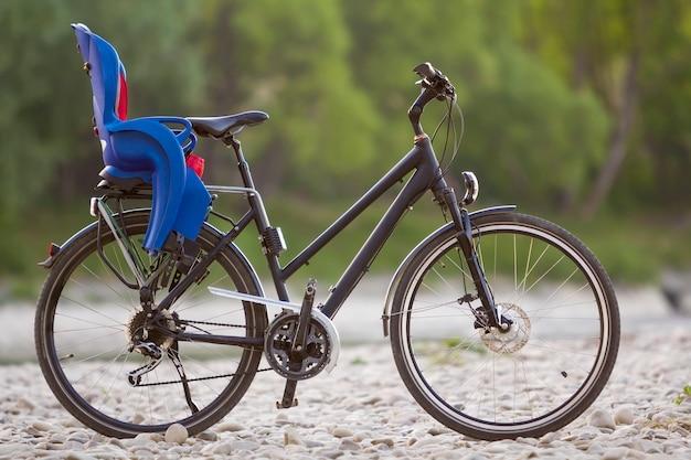 Nahaufnahme des neuen modernen schwarzen fahrrads mit dem blauen plastikkindersitz, der auf der seite steht, beleuchtet durch sonnenkiesel auf verschwommenem grünem baumsommerbokehhintergrund. tourismus- und familienreisekonzept.