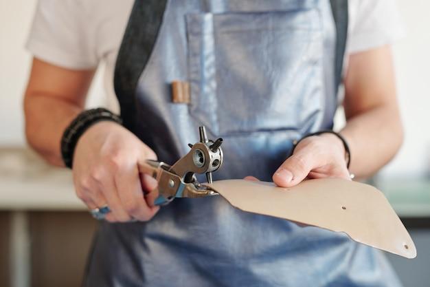 Nahaufnahme des nicht erkennbaren arbeiters in der schürze, die löcher in lederstück unter verwendung des drehwerkzeugs stanzt