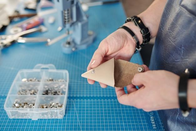 Nahaufnahme des nicht erkennbaren arbeiters mit armbändern, die lederprodukt mit druckknöpfen über schreibtisch mit behälter halten