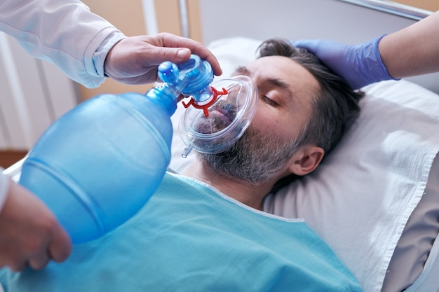 Nahaufnahme des nicht erkennbaren arztes, der beutelventilmaske auf gesicht des bewusstlosen patienten setzt