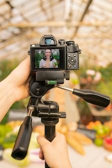 Nahaufnahme des nicht erkennbaren bedieners, der kamera auf einbeinstativ verwendet, um video mit asiatischer frau im gewächshaus zu schießen