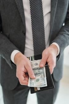 Nahaufnahme des nicht erkennbaren geschäftsmannes im grauen anzug, der geldbörse hält und bargeld für die zahlung vorbereitet