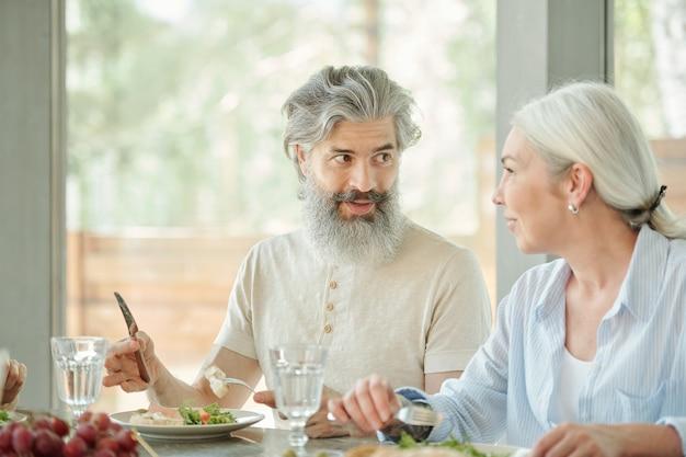Nahaufnahme des nicht erkennbaren mannes, der am tisch sitzt und erfrischenden salat mit gabel und messer isst