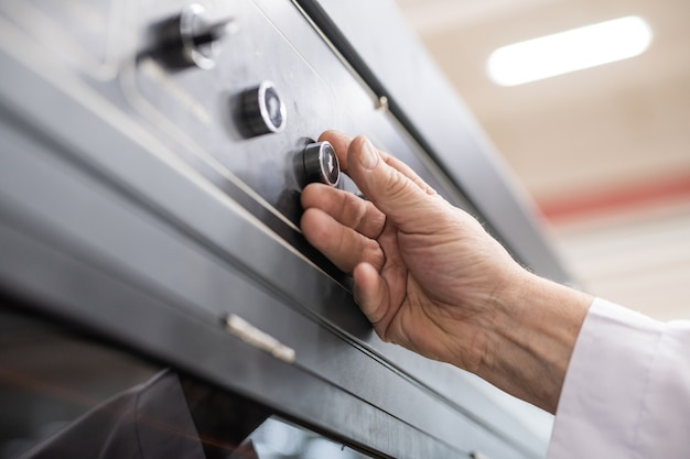 Nahaufnahme des nicht erkennbaren mannes, der knopf mit pfeil nach unten drückt, während automatisierte fabrikmaschine verwendet wird