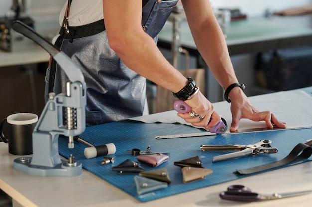 Nahaufnahme des nicht erkennbaren mannes in der schürze unter verwendung des metalllineals, um kante des leders im handwerksstudio zu schneiden