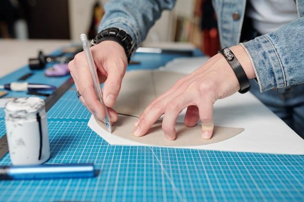 Nahaufnahme des nicht erkennbaren mannes mit armbändern unter verwendung von schnittmustern in der lederverarbeitung beim herstellen des lederartikels