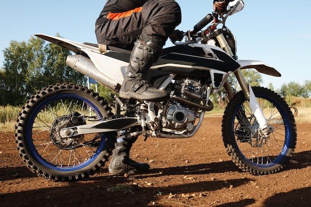Nahaufnahme des nicht erkennbaren motorradfahrers in hohen stiefeln, die fuß auf pedal halten, während sie sich auf das rennen vorbereiten