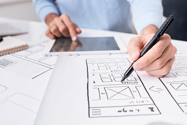 Nahaufnahme des nicht erkennbaren ui-ingenieurs unter verwendung eines digitalen tablets während der arbeit am app-planer-design für gadgets