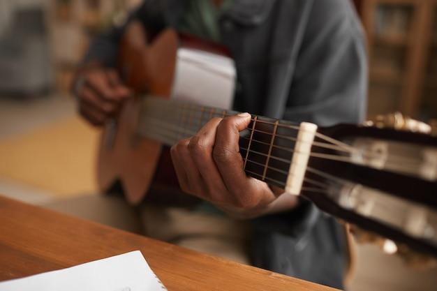 Nahaufnahme des nicht wiedererkennbaren afroamerikanischen mannes, der gitarre spielt, während musik zu hause genießt, kopieren raum