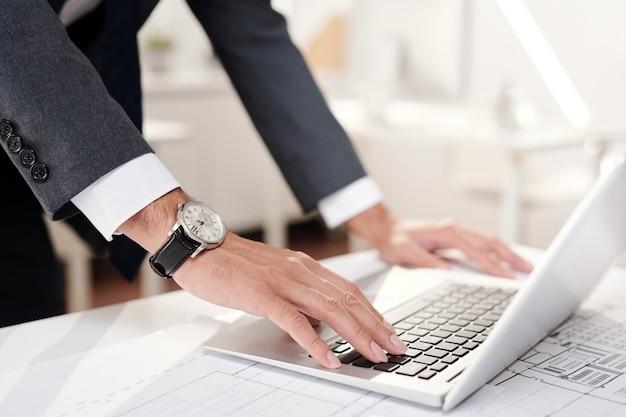 Nahaufnahme des nicht wiedererkennbaren erfolgreichen geschäftsmannes, der laptop verwendet und teure armbanduhr trägt, kopieren raum