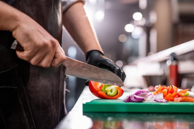 Nahaufnahme des nicht wiedererkennbaren kochs in der schürze, die paprika mit küchenmesser schneidet, während erfrischender sommersalat macht