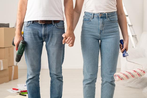 Nahaufnahme des nicht wiedererkennbaren paares in den jeans, die mit farbroller und kabellosem schraubendreher stehen, während renovierung in wohnung zusammen tun