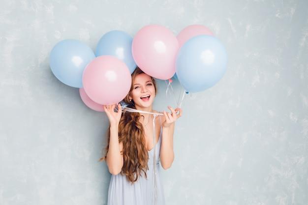 Nahaufnahme des niedlichen blonden mädchens, das in einem studio steht, breit lächelt und mit blauen und rosa luftballons spielt. sie hat spaß