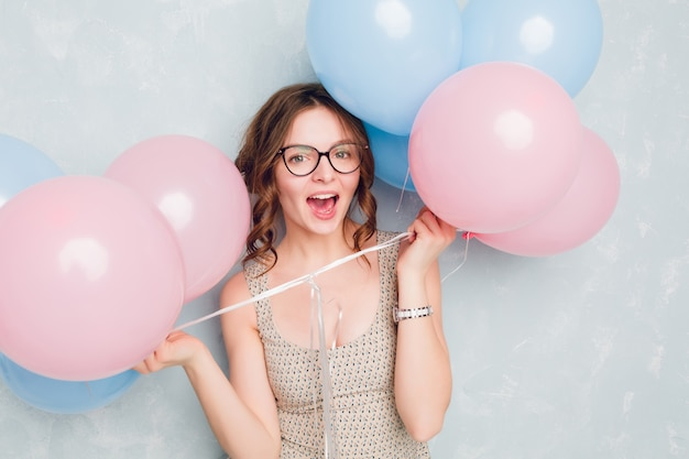 Nahaufnahme des niedlichen brünetten mädchens, das in einem studio steht, breit lächelt und mit blauen und rosa luftballons spielt. sie hat spaß