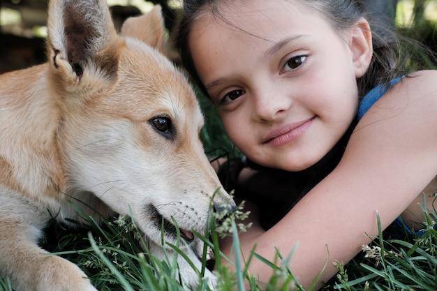 Nahaufnahme des niedlichen kleinen mädchens, das beim liegen auf dem gras mit dem hund schaut