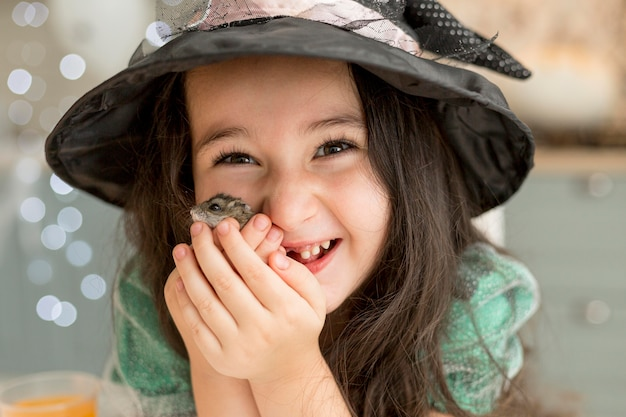 Nahaufnahme des niedlichen kleinen mädchens, das einen hamster hält