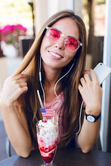 Nahaufnahme des niedlichen mädchens, das in einem café sitzt, das eis mit kirsche oben isst. sie trägt ein rosa oberteil und eine rosa brille. sie hört musik auf dem smartphone und lächelt. sie hat lange dunkle haare