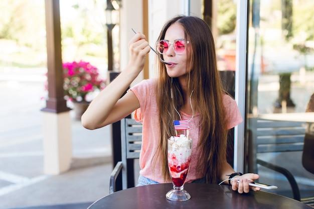 Nahaufnahme des niedlichen mädchens, das in einem café sitzt, das eis mit kirsche oben mit einem löffel isst. sie trägt jeansshorts, ein rosa top und lächelt. sie hat rosa brillen. sie hört musik auf dem smartphone