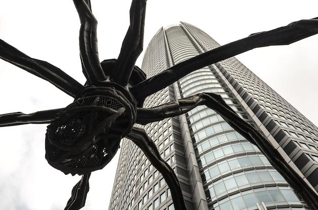 Nahaufnahme des niedrigen winkels der spinnenstatue durch den mori tower, tokio, japan