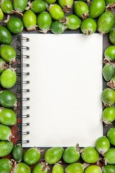Nahaufnahme des notebooks unter frischen natürlichen grünen feijoas