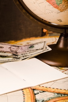 Nahaufnahme des notizblockes, der banknoten und der kugel auf karte