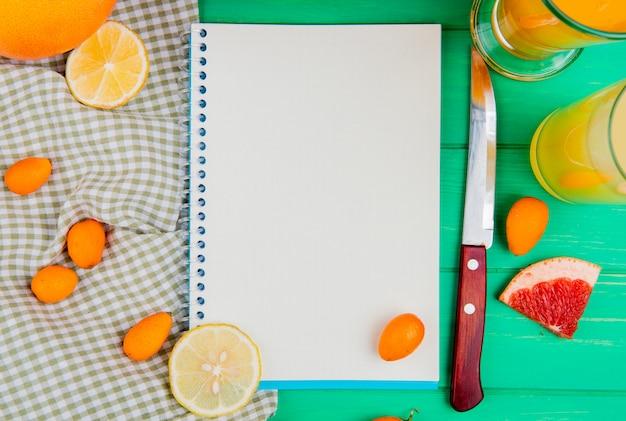 Nahaufnahme des notizblocks mit orangefarbenem zitronen-kumquat-grapefruitmesser und säften herum auf grünem hintergrund mit kopienraum
