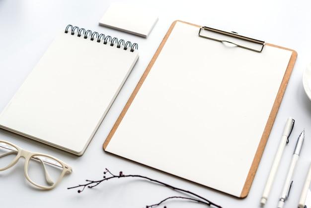 Nahaufnahme des notizbuches und des papiers getrennt auf weiß