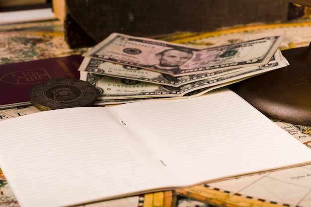 Nahaufnahme des offenen notizblockes mit banknoten und pass