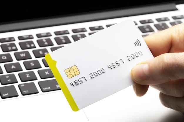 Nahaufnahme des online-käufers, der mit kreditkarte auf computertastatur mit kopienraum zahlt. online einkaufen.