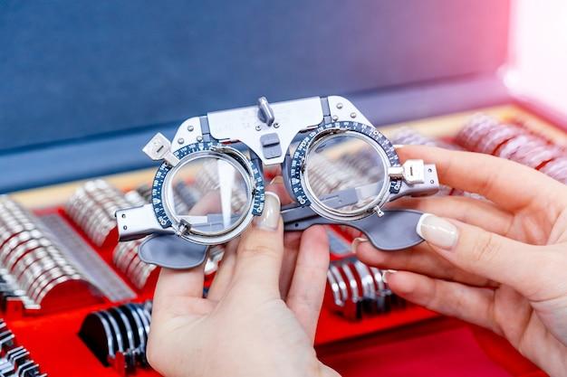 Nahaufnahme des ophthalmologischen versuchsrahmens und der testbrille in den händen der frau