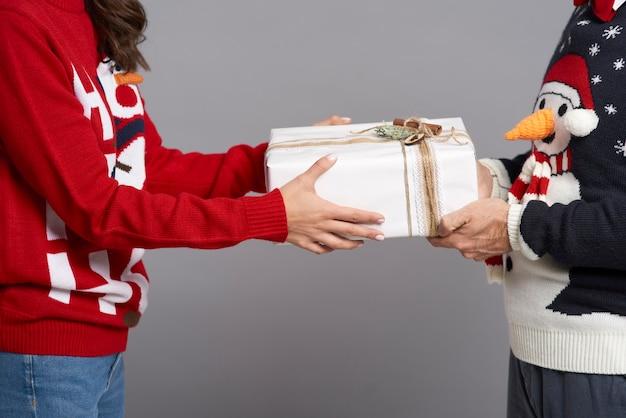 Nahaufnahme des paares, das weihnachtsgeschenk hält