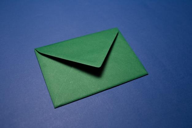 Nahaufnahme des papierumschlags der grünen farbe lokalisiert auf der strukturierten blauen wand.