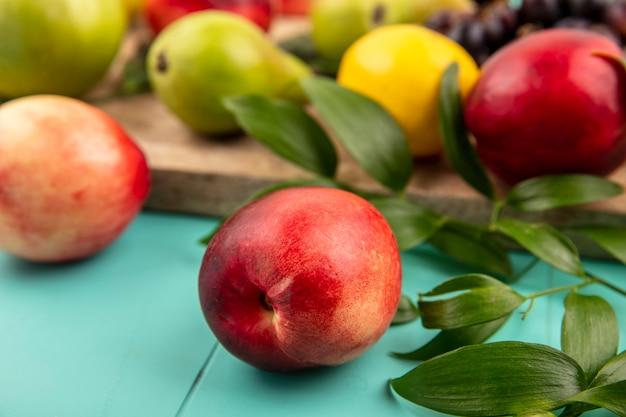 Nahaufnahme des pfirsichs mit blättern und birnenzitrone auf schneidebrett auf blauem hintergrund