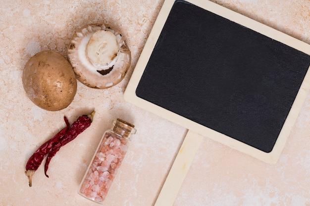 Nahaufnahme des pilzes; chilischoten und himalayasalzflasche nahe dem leeren hölzernen plakat