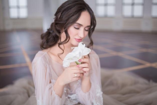 Nahaufnahme des porträts der schönen glücklichen braut im hochzeitskleid mit einer blume, die auf dem boden sitzt