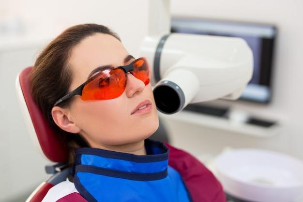Nahaufnahme des porträts einer attraktiven frau, die in der zahnarztpraxis mit zahnröntgen sitzt
