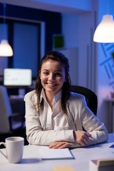 Nahaufnahme des porträts einer geschäftsfrau, die in die kamera lächelt, nachdem sie spät in der nacht eine tasse kaffee am schreibtisch im geschäftsbüro getrunken hat