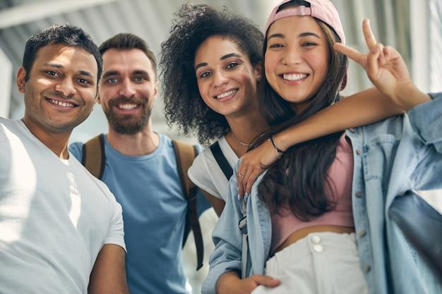 Nahaufnahme des porträts einer glücklichen, freundlichen gruppe in freizeitkleidung, die zusammen reist und am flughafen fotografiert?