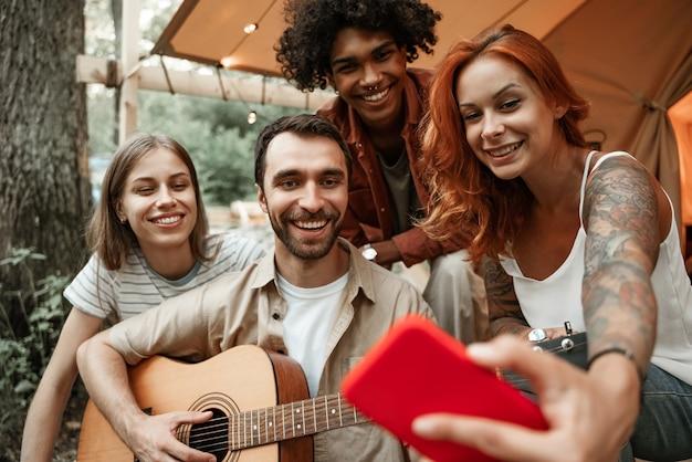 Nahaufnahme des porträts einer gruppe junger freunde, die zusammen im glamping im wald unterwegs sind und spaß beim gitarrespielen haben, selfies machen, zu sozialen medien streamen und lachen im zelt sitzen