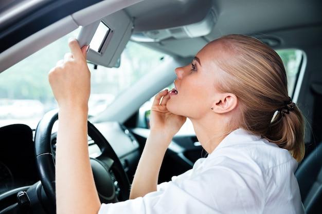 Nahaufnahme des porträts einer hübschen jungen geschäftsfrau, die beim autofahren in den spiegel schaut